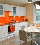 Белый гарнитур и оранжевая стена в интерьере кухни