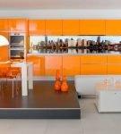 Гарнитур апельсинового цвета в большой кухне-гостиной