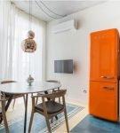Оранжевый холодильник в лаконичном интерьере кухни