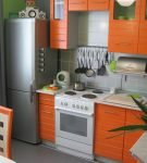 Небольшая кухня с оранжевой мебелью и холодильником