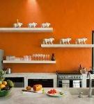 Белые полки на фоне оранжевой стены кухни