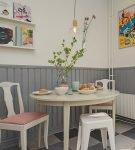 Серые панели и светлые обои около обеденного стола на кухне