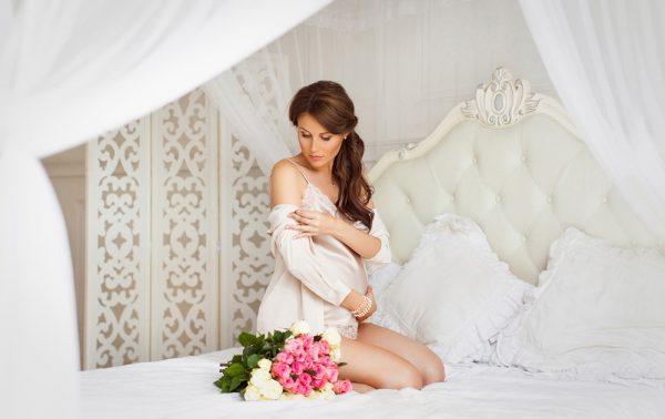 Беременная с красивыми волосами сидит на кровати