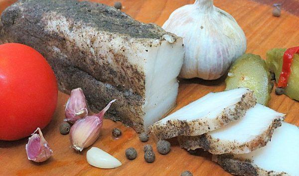 Ломтики солёного сала в чёрном молотом перце и овощи на деревянной поверхности