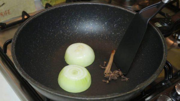 Половинки головки репчатого лука и специи на сковороде с лопаточкой
