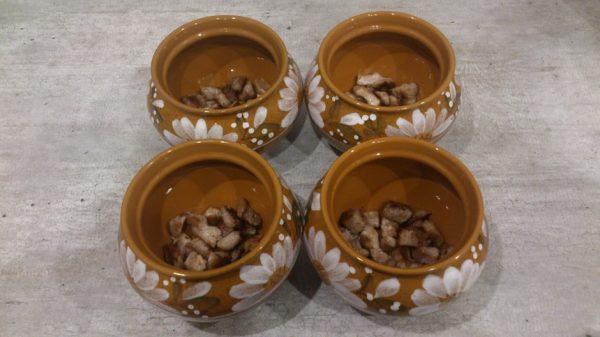 Кусочки обжаренного мяса в порционных керамических горшочках