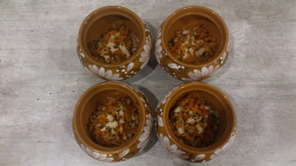 Мясо, обжаренные овощи и рубленый чеснок в керамических горшочках