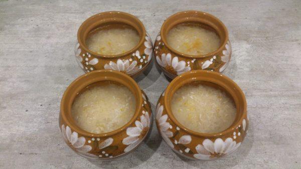 Залитый водой сырой рис в керамических горшочках