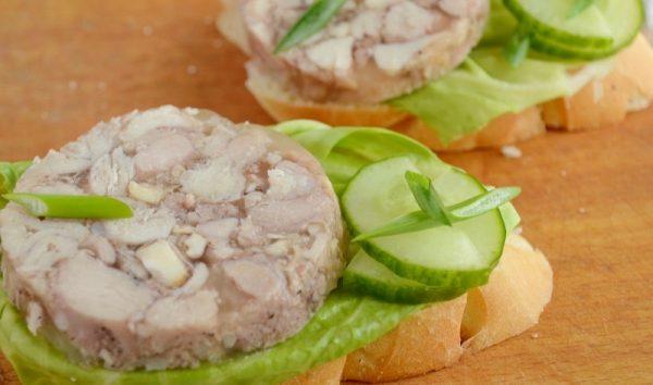 Бутерброды из батона с листьями салата и кружочками куриного рулета с желатином в бутылке