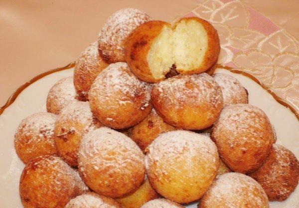 Посыпанные сахарной пудрой творожные пончики на тарелке