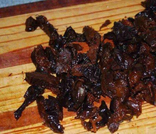 Мелко нарезанный чернослив на деревянной разделочной доске