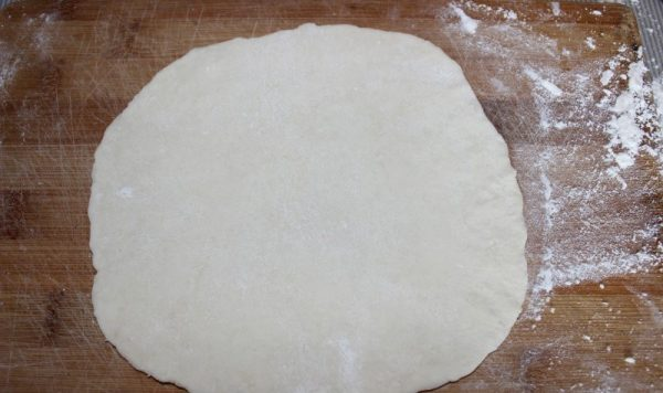 Раскатанное в пласт тесто на разделочной доске