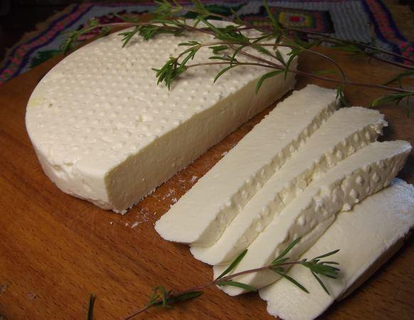 Нарезанный ломтиками адыгейский сыр с зеленью на деревянной разделочной доске