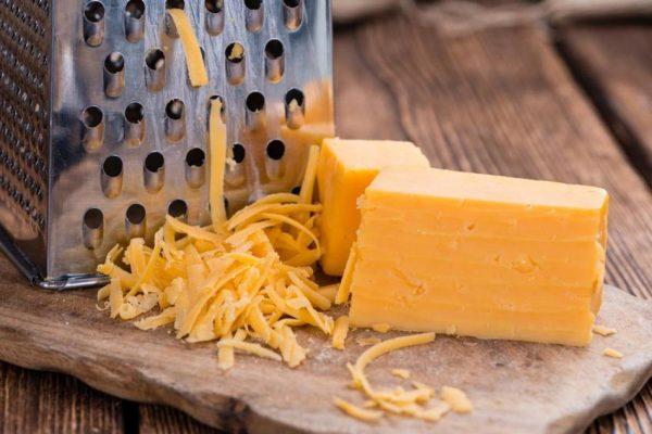 Кусок сыра рядом с тёркой