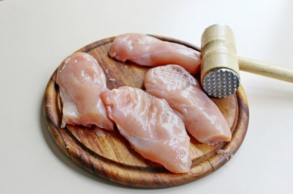 Кусочки сырого куриного филе и молоток для мяса на круглой разделочной доске