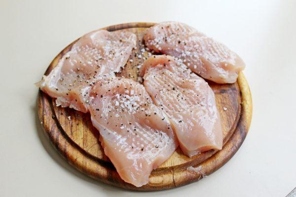 Поспанные солью и чёрным молотым перцем кусочки куриного филе на разделочной доске