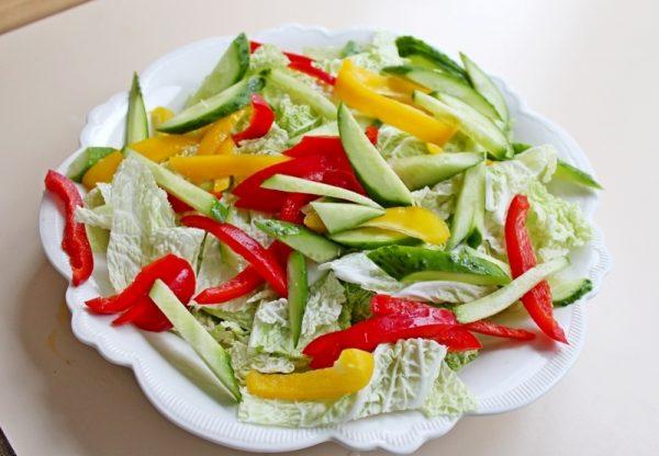 Пекинская капуста и нарезанные соломкой свежие овощи на большой тарелке