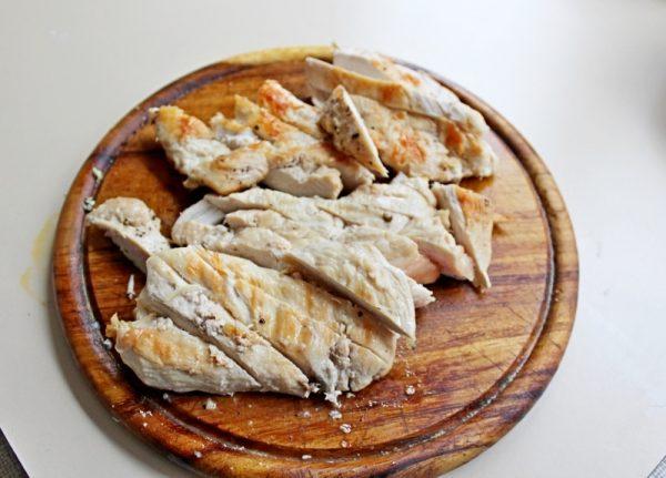 Нарезанное полосками обжаренное куриное филе на разделочной доске
