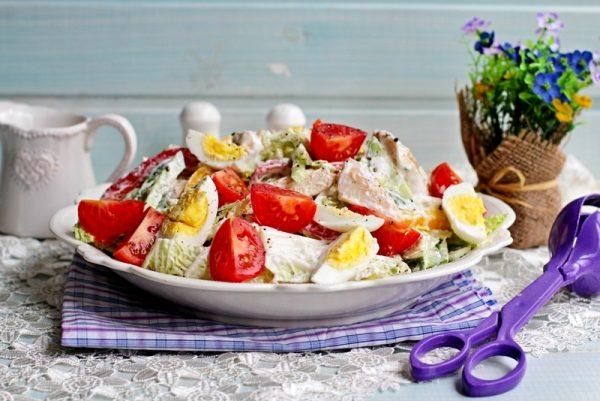 Салат с куриной грудкой и пекинской капустой в тарелке на сервированном столе