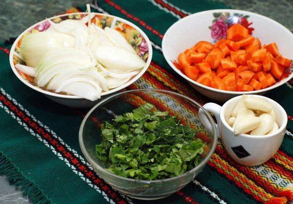 Подготовленные овощи и свежая зелень в разных ёмкостях на столе