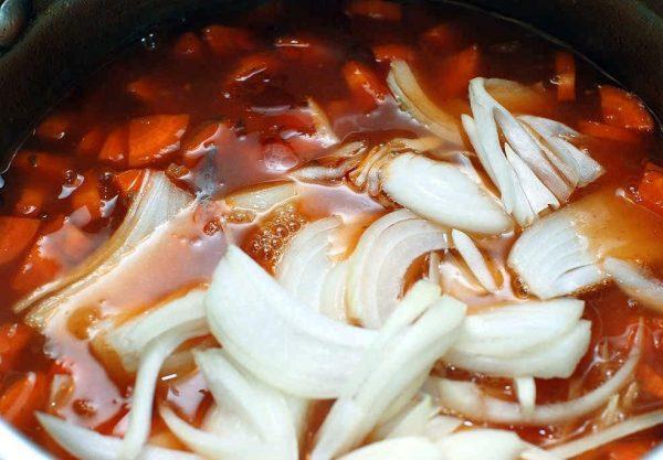 Репчатый лук и морковь в кастрюле с супом