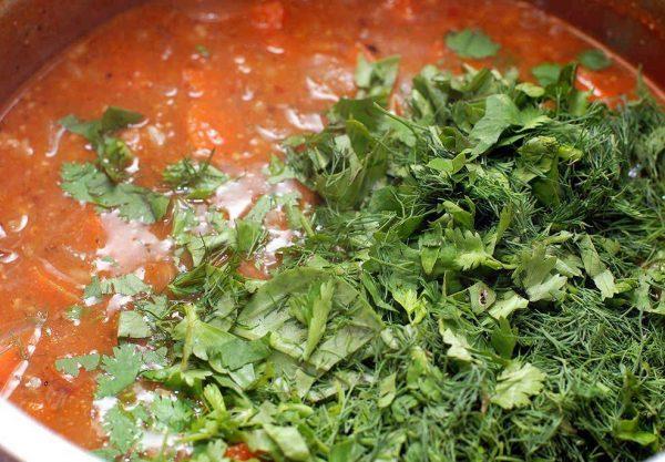 Свежая рубленая зелень в кастрюле с супом