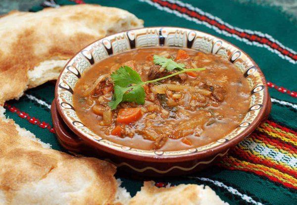 Грузинский суп харчо в тарелке на столе с лавашем
