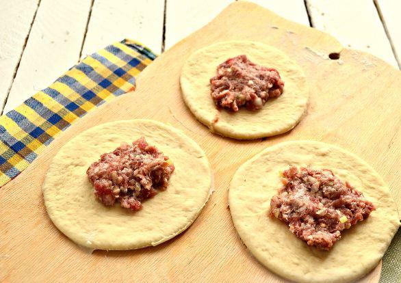 Кружочки из сырого теста с мясной начинкой на разделочной доске