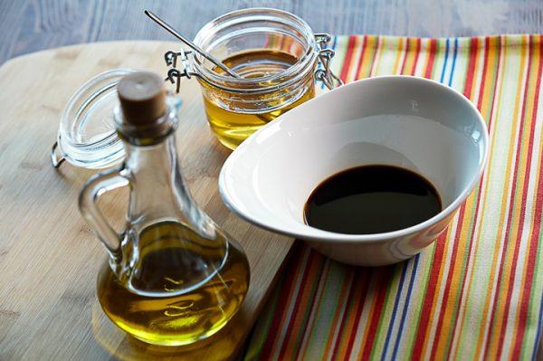 Оливковое масло, жидкий мёд и бальзамический уксус на столе