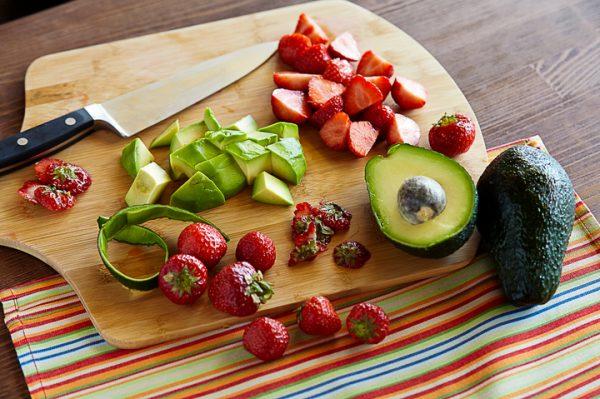 Нарезанные кусочками ягоды клубники и авокадо на деревянной разделочной доске