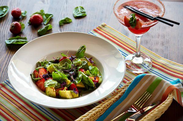 Салат из авокадо и клубники на красиво сервированном столе