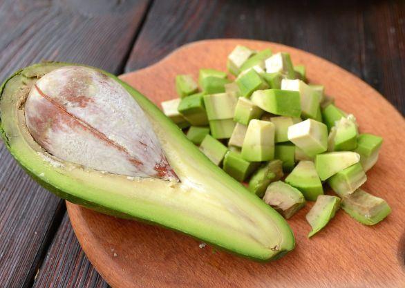 Половинка авокадо и кусочки фрукта на деревянной разделочной доске