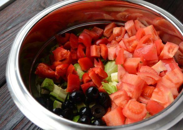 Подготовленные ингредиенты для салата из авокадо с овощами в глубокой ёмкости