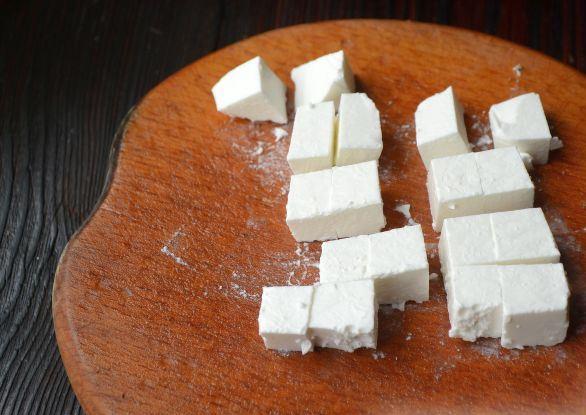 Нарезанный кубиками сыр фета на разделочной доске
