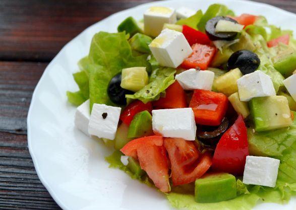Готовый салат из авокадо с овощами и сыром на большой белой тарелке