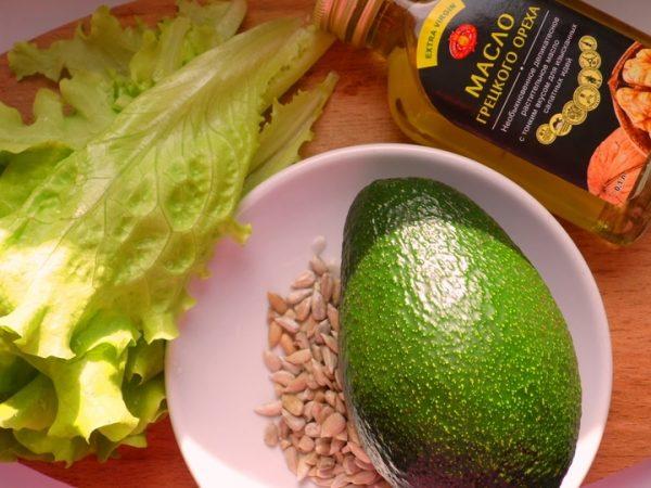 Листья салата, авокадо и семена подсолнечника в тарелке, бутылка с ореховым маслом на столе