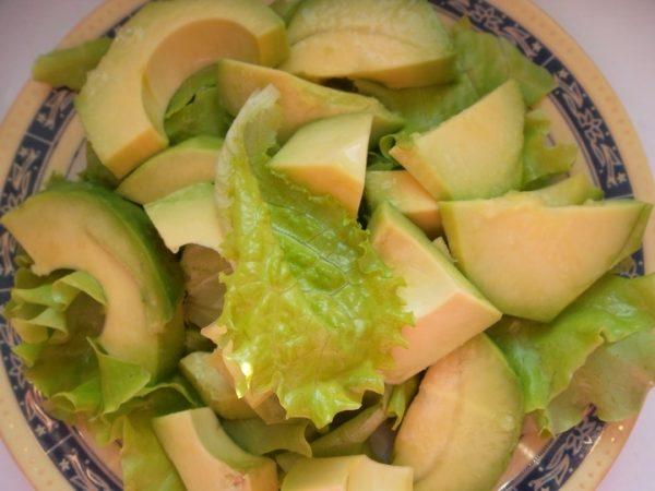 Ломтики авокадо и кусочки салатных листьев в небольшой тарелке