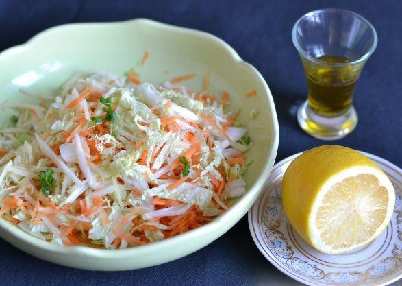 Салат из пекинской капусты в миске, лимон на блюдечке и оливковое масло в рюмке