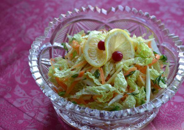 Салат из пекинской капусты с яблоком и морковью в стеклянном салатнике на столе