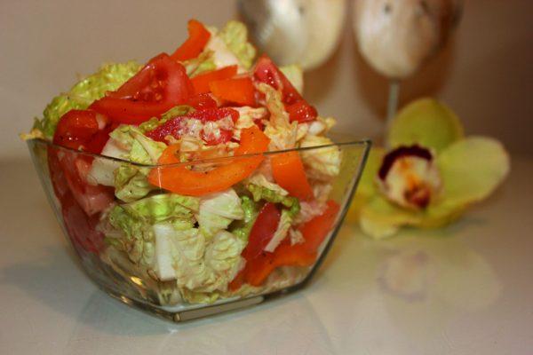 Салат из пекинской капусты с овощами в маленьком стеклянном салатнике на столе