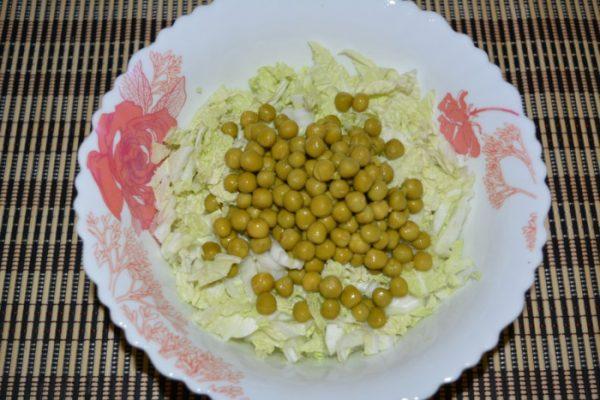 Консервированный зелёный горошек и нарезанная полосками пекинская капуста в тарелке на столе