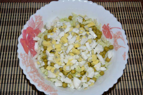 Нарезанные кубиками варёные яйца в тарелке с пекинской капустой и консервированным горошком
