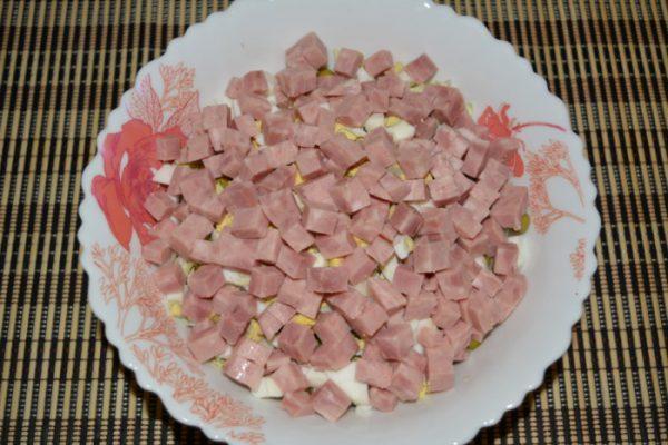 Нарезанная кубиками ветчина в тарелке с заготовкой для салата