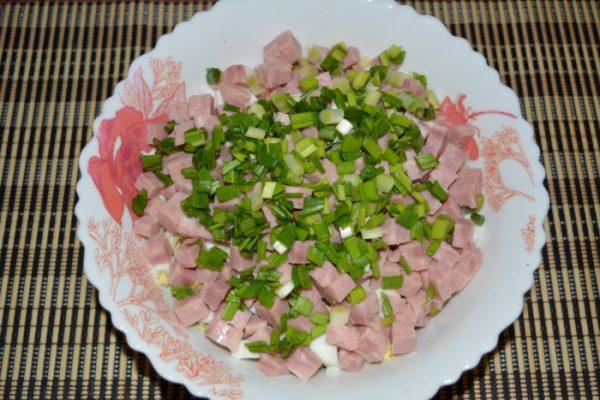 Зелёный лук в тарелке с кубиками ветчины и другими ингредиентами салата из пекинской капусты