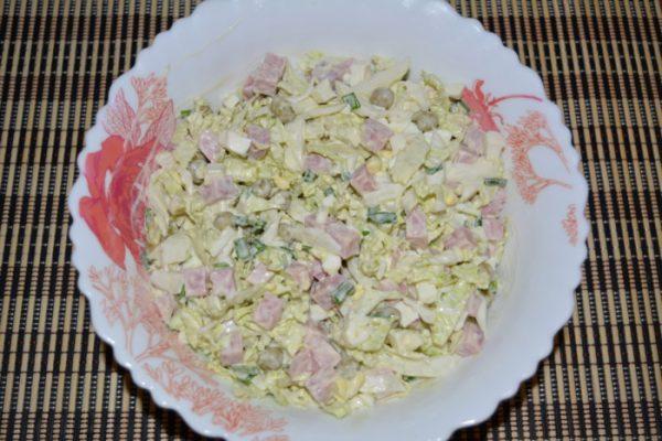 Салат из пекинской капусты с ветчиной, горошком и майонезом в тарелке