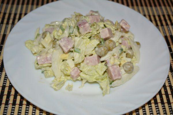 Салат из пекинской капусты с горошком и ветчиной в порционной белой тарелке