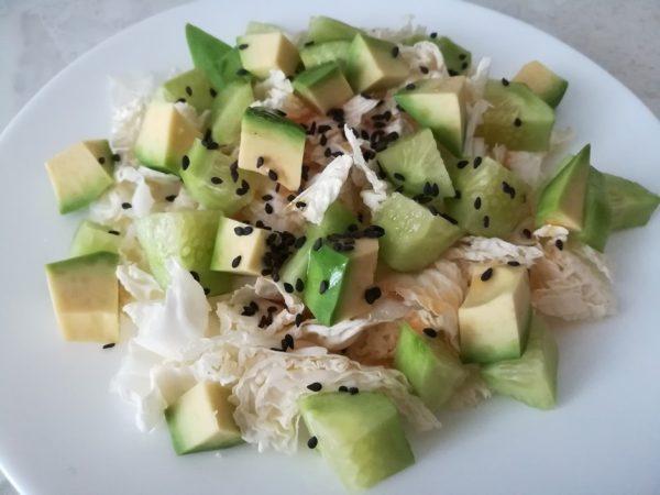 Салат из пекинской капусты с огурцом, авокадо и кунжутом на белой тарелке