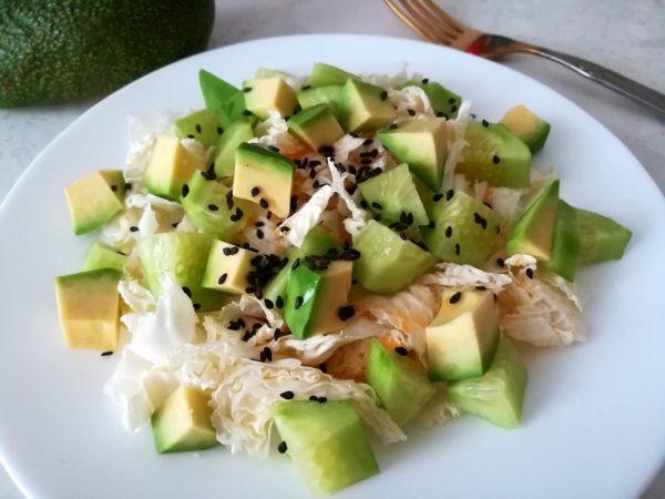 Готовый салат из пекинской капусты с авокадо, свежим огурцом и чёрным кунжутом на тарелке