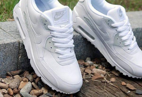 Белые кроссовки на бордюре