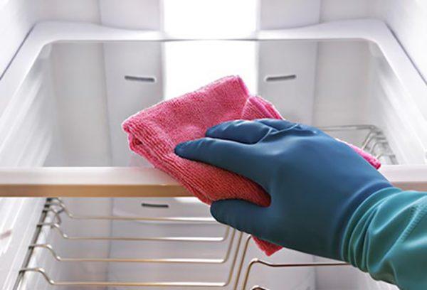 Вытирают холодильник салфеткой